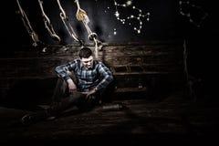O homem desapontado senta-se perto de uma caixa, guardando a garrafa de vidro e a tentativa foto de stock royalty free