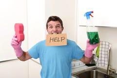 O homem desarrumado no esforço nas luvas de lavagem que guardam o pulverizador da esponja e do detergente engarrafa pedir a ajuda fotos de stock royalty free
