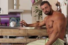 O homem descamisado do licenciado do músculo tem um café da manhã na cozinha Foto de Stock Royalty Free