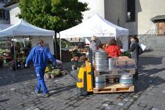 O homem descarrega tambores de cerveja na lucerna Imagens de Stock