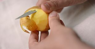 O homem descasca manualmente batatas com uma faca de tabela foto de stock