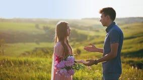 O homem desculpa-se à menina, a mulher irritada bate o indivíduo e joga flores nele e nas folhas vídeos de arquivo