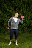 O homem desportivo está exercitando com pesos 5kg fora em um verde Imagem de Stock