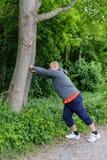 O homem desportivo que faz o esticão exercita na floresta em uma árvore Foto de Stock