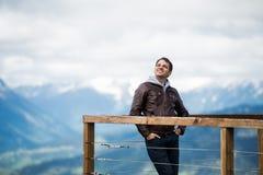O homem despreocupado e livre feliz que olha a um céu com mãos em seus bolsos sobre cumes da montanha ajardina Fotografia de Stock