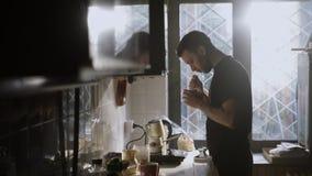 O homem dirige sua xícara de café e cheira o aroma filme