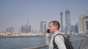O homem disca o número no telefone e fala no fundo do panorama de Dubai Close-up da mão vídeos de arquivo