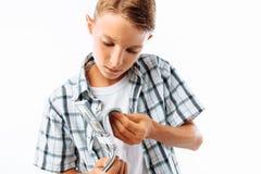 O homem disse as contas com cem dólares, o adolescente obteve seu primeiro dinheiro ganhado no estúdio em um fundo branco fotos de stock