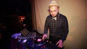O homem DJ no chapéu no DJ almofada nightclub vídeos de arquivo