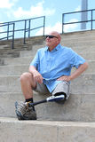 O homem do amputado assentado com pé e prótese cruzou-se, mão no quadril imagens de stock royalty free
