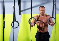 O homem do anel do mergulho de Crossfit relaxou após o exercício no gym Imagem de Stock Royalty Free