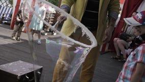 O homem do animador faz a bolha de sabão grande posta dentro sobre o menino no terraço do restaurante Miúdos video estoque