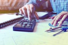 O homem do arquiteto calcula a área de construção no modelo no escritório foto de stock royalty free