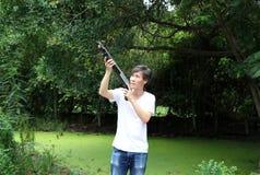 O homem do artilheiro que está a arma longa que aponta o direito superior lateralmente com brim branco da camisa e da sarja de Ni fotografia de stock