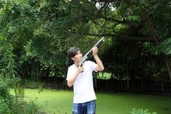 O homem do artilheiro que está a arma longa que aponta o superior esquerdo lateralmente com brim branco da camisa e da sarja de N imagens de stock