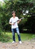 O homem do artilheiro que guarda a arma longa nas mãos e girada à esquerda lateralmente com o brim branco da camisa e da sarja de fotos de stock royalty free