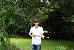 O homem do artilheiro que guarda a arma longa nas mãos e girada à esquerda lateralmente com o brim branco da camisa e da sarja de imagem de stock
