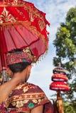 O homem do Balinese nos sarongues guarda o guarda-chuva no templo hindu foto de stock