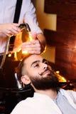 O homem do cabeleireiro lava o cliente Foto de Stock