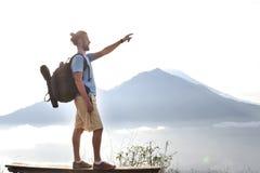 O homem do caminhante com trouxa aprecia com vulcão Batur, Indonésia Fotos de Stock