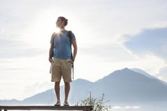 O homem do caminhante com trouxa aprecia com vulcão Batur, Indonésia Imagens de Stock