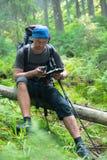 O homem do caminhante está descansando e determina sua posição na floresta w Imagem de Stock Royalty Free