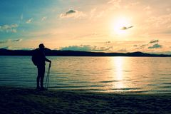 O homem do caminhante no sportswear escuro e com a trouxa desportiva que está na praia, relaxando e aprecia o por do sol no horiz Imagem de Stock Royalty Free