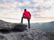 O homem do caminhante toma um resto no pico de montanha O homem coloca na cimeira, vale do outono do fole fotos de stock royalty free