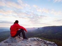 O homem do caminhante toma um resto no pico de montanha O homem coloca na cimeira, vale do outono do fole foto de stock