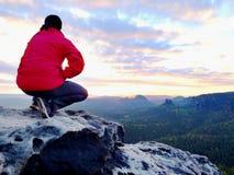 O homem do caminhante toma um resto no pico de montanha O homem coloca na cimeira, vale do outono do fole Sol brilhante da manhã foto de stock royalty free
