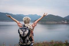 O homem do caminhante do viajante com aumento da trouxa entrega perto do lago Turista fotos de stock