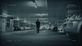 O homem do CCTV anda ao carro na garagem de estacionamento