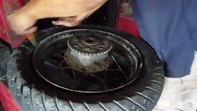O homem do close up limpa o pneu decola da máquina do equilíbrio filme