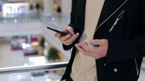 O homem do close-up paga por compras pelo cartão de crédito usando o telefone em uma alameda video estoque