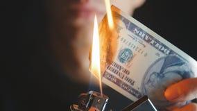 O homem do close-up queima uma nota de dólar em um fundo escuro video estoque