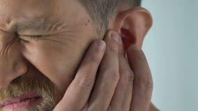 O homem do envelhecimento tem a dor da orelha após ter travado o esboço, infecção bacteriana, dor do otitis filme