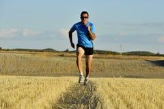 O homem do esporte com os óculos de sol que correm fora no campo da palha moeu na perspectiva frontal fotografia de stock
