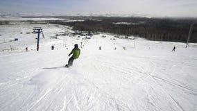 O homem do esqui desce em um snowboard no tempo ensolarado em uma inclinação nevado video estoque