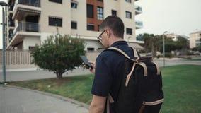 O homem do estudante com trouxa e telefone está andando na jarda perto das construções, opinião da parte traseira video estoque