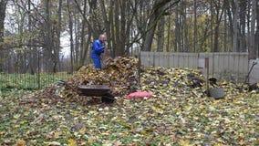 O homem do fazendeiro leva o saco do saco do carrinho de mão completamente de folhas e despeja-o na pilha do adubo 4K vídeos de arquivo