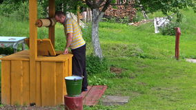 O homem do fazendeiro na água boa da tração da casa e derrama na cubeta video estoque