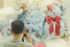 O homem do fotógrafo toma a foto da árvore de Natal decorada e de um sn fotografia de stock royalty free