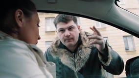 O homem do gângster no casaco de cabedal força a mulher que senta-se no carro à janela aberta filme