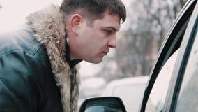 O homem do gangster leva embora aproximadamente algo do motorista que senta-se no carro video estoque