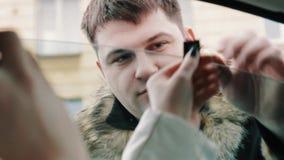 O homem do gangster no casaco de cabedal força a mulher que senta-se no carro à janela aberta vídeos de arquivo