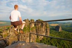 O homem do gengibre senta-se no corrimão no pico da rocha e olha-se para ajardinar Dia ensolarado em montanhas rochosas Caminhant Imagem de Stock Royalty Free