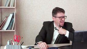 O homem do gestor de escritório com barba está quente no trabalho suar vídeos de arquivo