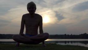 O homem do iogue senta-se em uns lótus e levanta-se seu corpo no por do sol no slo-mo filme