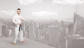 O homem do karaté que faz o karaté engana na parte superior de uma cidade metropolitana Imagens de Stock Royalty Free