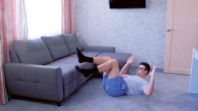 O homem do lerdo está fazendo triturações abdominais exercita a colocação no assoalho que respira dentro e para fora em casa Conc vídeos de arquivo